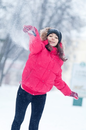 Happy young woman plays with a snow outdoor. Winter day Stock Photo - 18207930