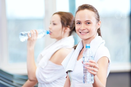 Two young women drinking water after sports. Fitness gym. Stock Photo - 18440277