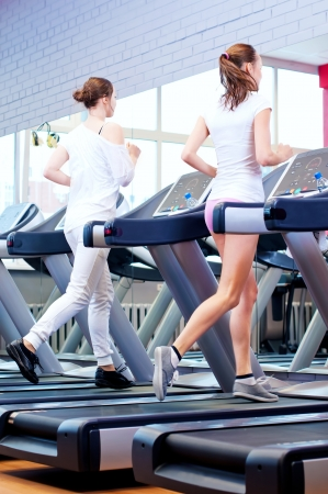 Two young sporty women run on machine in the gym centre Stock Photo - 18440256