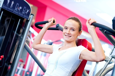 Woman doing fitness training on a butterfly machine with weights in a gym  Stock Photo - 18440259