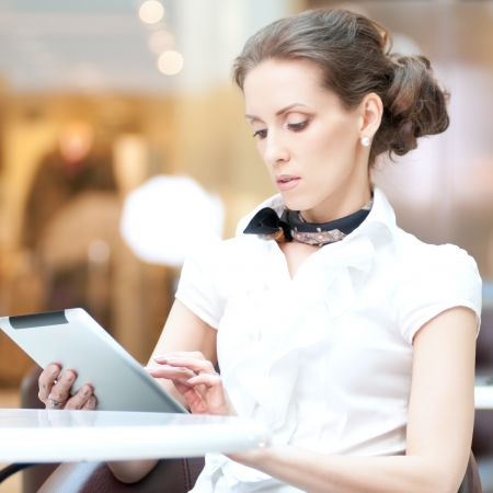 Young professional businesswoman sitting at table at cafe and using tablet on lunch break Stock Photo - 18435545