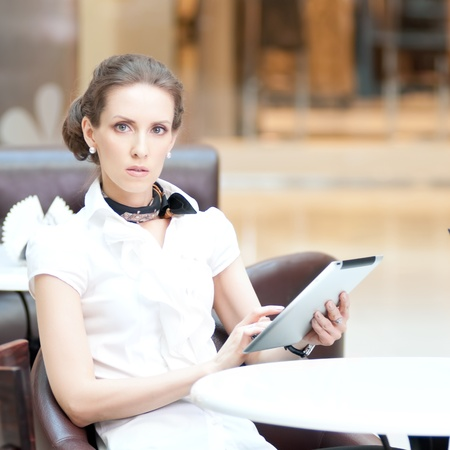 Young professional businesswoman sitting at table at cafe and using tablet on lunch break Stock Photo - 18440267