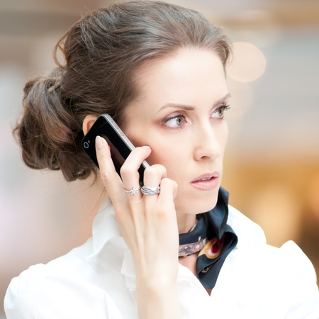 Beautiful business woman talking on cell phone over business background Stock Photo - 18440261