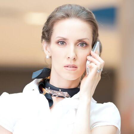 Beautiful business woman talking on cell phone over business background photo