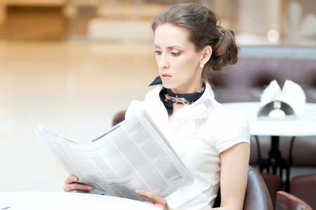 Serious business woman in cafe reading newspaper while lunch time Stock Photo - 18440241
