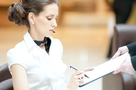 Business woman sign documents: writing with pen Stock Photo - 18440252