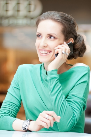 Beautiful business woman talking on cell phone over business background Stock Photo - 18440233