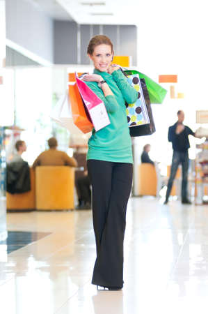 Happy woman with shopping bags in mall center. Sales. Stock Photo - 18440262