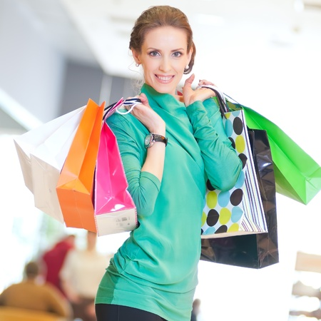 Happy woman with shopping bags in mall center. Sales. Stock Photo - 18440257