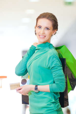 Happy woman with shopping bags and credit card in mall center. Sales. Stock Photo - 18440250