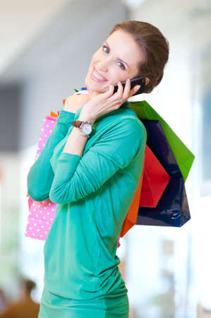 Happy woman with shopping bags in mall center talking by phone. Sales. Stock Photo - 18440245