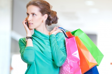 Happy woman with shopping bags in mall center talking by phone. Sales. Stock Photo - 18440243