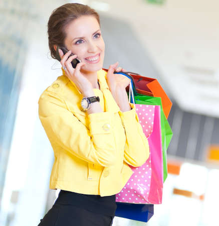 Happy woman with shopping bags in mall center talking by phone. Sales. Stock Photo - 18440268