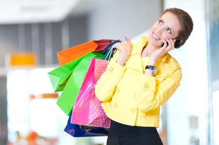 Happy woman with shopping bags in mall center talking by phone. Sales. Stock Photo - 18440264