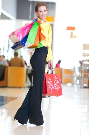 Happy woman with shopping bags in mall center. Sales. Stock Photo - 18440265