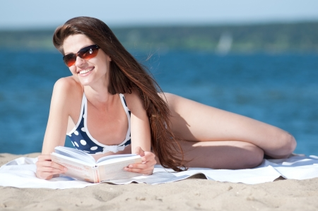 Close up of a beautiful young woman reading book on beach photo