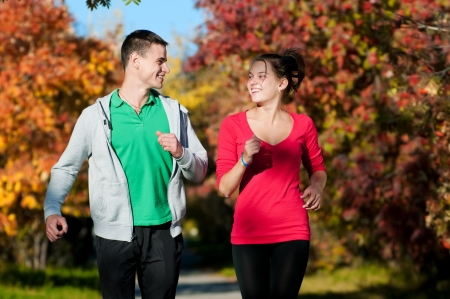 Young fitness couple of man and woman jogging in park  Stock Photo - 19083722