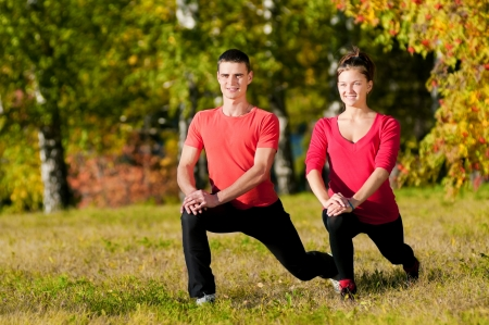 Young man and woman woman doing yoga in the sunny summer park Stock Photo - 19083732