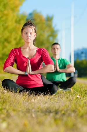 Young man and woman woman doing yoga in the sunny summer park Stock Photo - 19083724