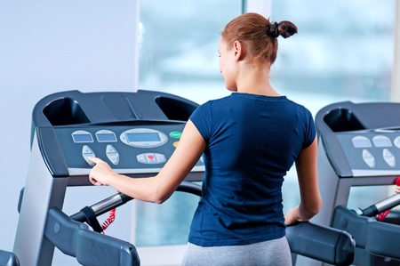 Young woman at the gym exerce. Jog on machine Stock Photo - 19083706