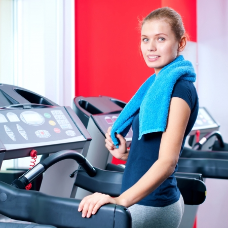 Young woman at the gym exercising. Run on machine Stock Photo - 19083704
