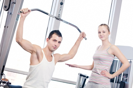 Gym man and woman doing exercise at the fitness club. Personal trainer. Stock Photo - 19083717
