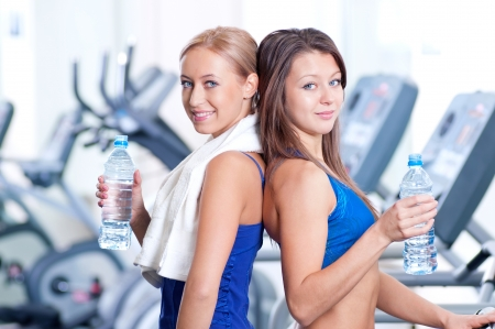 Two young women drinking water after sports. Fitness gym. Stock Photo - 19083693