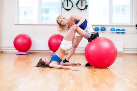 Two smiling women do stretching exercise in sports club. Fitness gym Stock Photo - 19083733