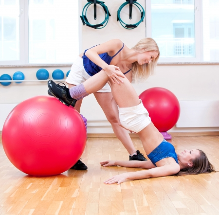 Two smiling women do stretching exercise in sports club. Fitness gym Stock Photo - 19083686