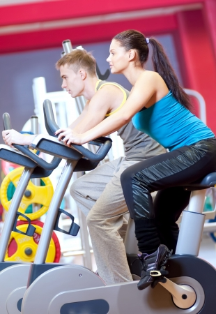 Group of two people in the gym, exercising their legs doing cardio cycling training  Stock Photo - 19083695
