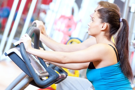 Group of two people in the gym, exercising their legs doing cardio cycling training  Stock Photo - 19083715