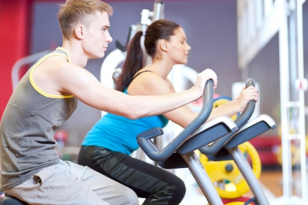 Group of two people in the gym, exercising their legs doing cardio cycling training  Stock Photo - 19083689