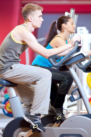 Group of two people in the gym, exercising their legs doing cardio cycling training Stock Photo - 19083701