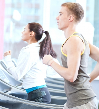 workout gym: Young woman and man at the gym exercising. Run on a machine.