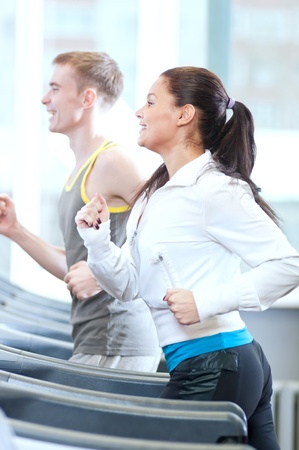 Young woman and man at the gym exercising. Run on a machine. Stock Photo - 19083702