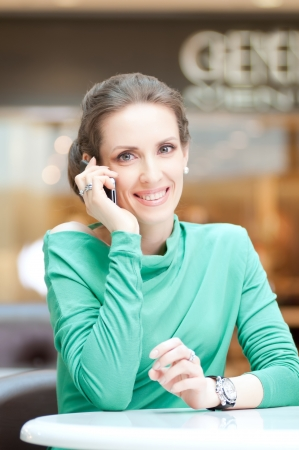 Beautiful business woman talking on cell phone over business background Stock Photo - 19083723