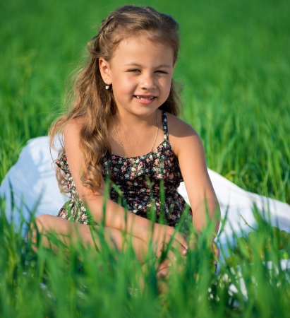 Happy girl on green grass at spring or summer park picnic Stock Photo - 19083741