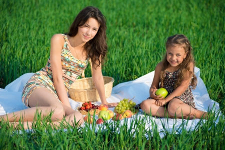 Happy girlswith fruits on green grass at spring or summer park picnic Stock Photo - 19083700