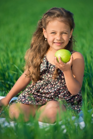 Happy girl with apple on green grass at spring or summer park picnic Stock Photo - 19083746