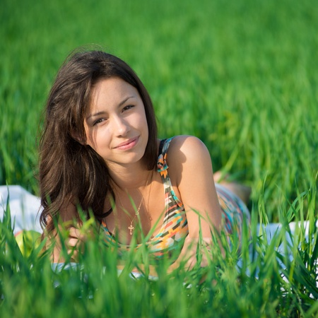 Happy girl on green grass at spring or summer park picnic Stock Photo - 19083744