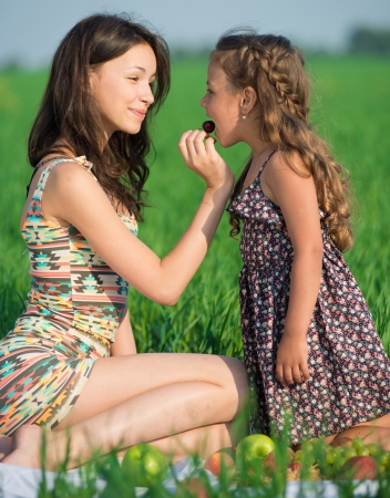 Happy girls eating cherry on green grass at spring or summer park picnic Stock Photo - 19083737