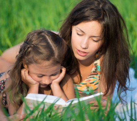 Happy girls reading book on green grass at spring or summer park picnic Stock Photo - 19083742