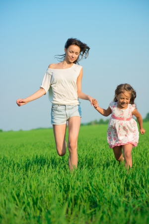 Young happy girls running down green wheat field with her friend together Stock Photo - 19083735