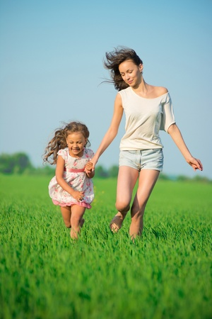 Young happy girls running down green wheat field with her friend together Stock Photo - 19083734