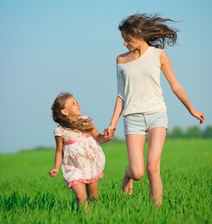 Young happy girls running down green wheat field with her friend together Stock Photo - 19083738