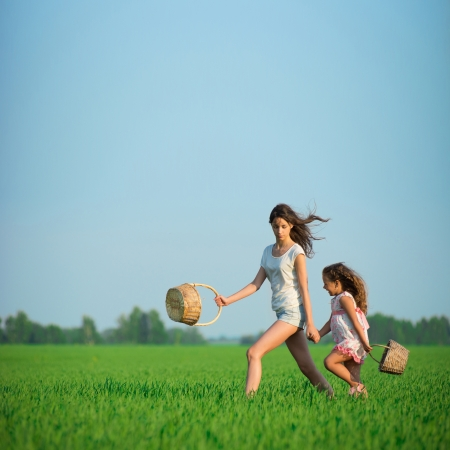 Young happy girls running with basket at green wheat field with her friend together Stock Photo - 19083747