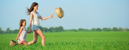 Young happy girls running with basket at green wheat field with her friend together Stock Photo - 19083739