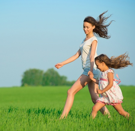 Young happy girls running down green wheat field with her friend together Stock Photo - 19083751