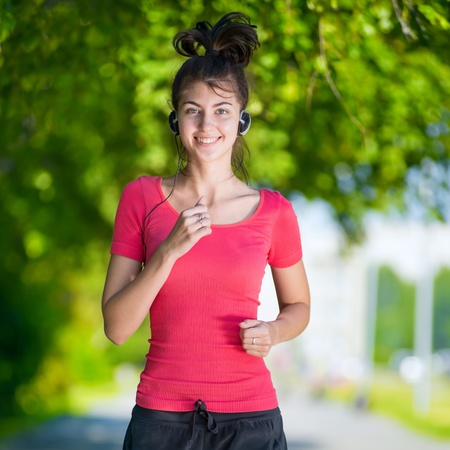 Young woman running outdoors in green park at lovely sunny summer day. Jogging with headphones and music photo