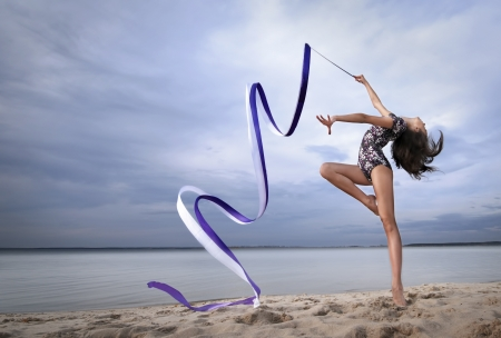 gymnastics sports: young professional gymnast woman dance with ribbon - outdoor sand beach